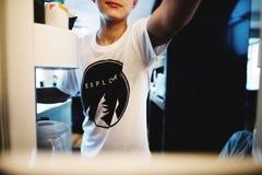 De jonge Kaukasische jongen opent de koelkast zoekend iets aan ea stock foto