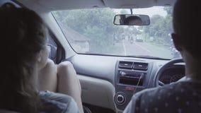 De jonge Kaukasische kerel en het meisje zitten in auto en rit op landelijk oostelijk tropisch gebied stock footage