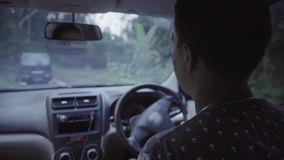 De jonge Kaukasische korte haired mens drijft rechtse aandrijvingsauto in landelijke weg stock videobeelden