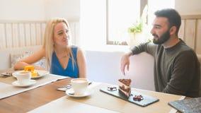 De jonge Kaukasische man voor vrouw probeert desserts in de koffie royalty-vrije stock foto's