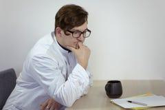 De jonge Kaukasische mannelijke arts in een witte uitrusting zit nadenkend, houdend zijn kin, met kop thee of koffie en documente stock foto's