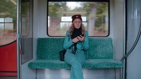 De jonge Kaukasische meisjesritten in een metro of tramtreinauto, gebruikt de telefoon, drukt een bericht Langzame Motie stock video