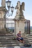 De jonge Kaukasische mensenspelen hangen trommel op de treden aan een engelenstandbeeld in Avignon, Frankrijk stock fotografie