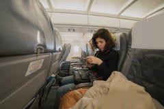 De jonge Kaukasische mobiele telefoon van het vrouwengebruik binnen vliegtuigzitting Royalty-vrije Stock Foto's