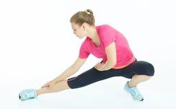 De jonge Kaukasische opwarming van vrouwen uitrekkende benen Stock Foto's