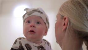 De jonge Kaukasische vrouw houdt de baby binnen voorzijde van camera in studio indient stock footage