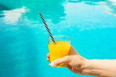 De jonge Kaukasische Vrouw houdt Glas vers Gedrukt Jus d'orange met Zwart-wit Gestreept Stro door de Zwembadzomer royalty-vrije stock afbeelding