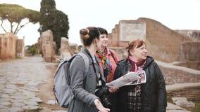 De jonge Kaukasische vrouwelijke gids die van de excursiereis detail op historische ruïnes van Ostia, Italië aan twee hogere vrou stock footage