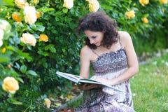 De jonge Kaukasische vrouwenzitting op groen gras dichtbij gele rozen ringt in een roze tuin, lezing een boek, kijkend aan het bo stock foto's