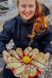 De jonge Kaukasische witte vrouw met rood haar houdt in haar handen een plaat met oesters en citroen stock afbeeldingen