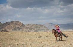 De jonge Kazakh dame van de adelaarsjager op haar paard Royalty-vrije Stock Foto