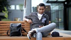 De jonge kerel babbelt een bericht voor zijn klasgenoten in zijn mobiele telefoon Hij zit op een beanch voor van hem stock videobeelden