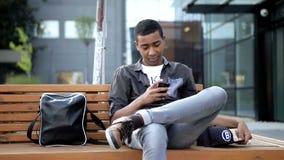 De jonge kerel babbelt een bericht voor zijn klasgenoten in zijn mobiele telefoon Hij zit op een beanch voor van hem stock video