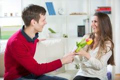 De jonge kerel brengt bloemen aan zijn meisje Royalty-vrije Stock Foto's