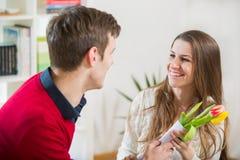 De jonge kerel brengt bloemen aan zijn meisje Stock Afbeelding