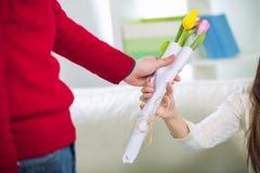 De jonge kerel brengt bloemen aan zijn meisje Royalty-vrije Stock Afbeelding