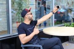 De jonge kerel de Arabische mannelijke mens selfie maakt, spreekt op Skype, glimlachen en Stock Afbeelding