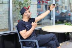 De jonge kerel de Arabische mannelijke mens selfie maakt, spreekt op Skype, glimlachen en Royalty-vrije Stock Foto