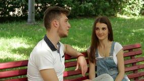 De jonge kerel flirt en amuseert het meisje in het Park op een bank stock videobeelden