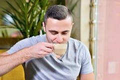 De jonge kerel is freelancer in koffie die achter laptop werken Het Drinken van de mens Koffie stock foto
