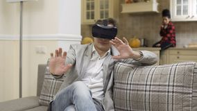 De jonge kerel gebruikt virtuele werkelijkheidsglazen en strijden met iemand stock footage