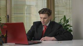 De jonge kerel in het kostuumwerk aangaande laptop en strijd met de afhankelijkheid van het roken, bereikt voor een sigaret 60 fp stock video