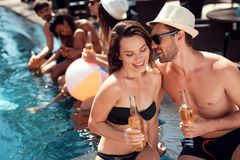 De jonge kerel in de hoed van het de zomerstro flirt met meisje in zwempakzitting in pool Zwembadpartij royalty-vrije stock foto's