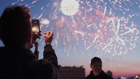 De jonge kerel houdt een smartphone met het fonkelen licht en het registreren van een video van vuurwerk op het dak Vrienden stock footage