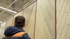 De jonge kerel kiest een vloerbedekking, een laminaat, in een winkel van bouwmaterialen stock video