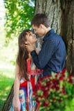 De jonge kerel koestert affectionately meisje in een zonnige aard Royalty-vrije Stock Afbeelding