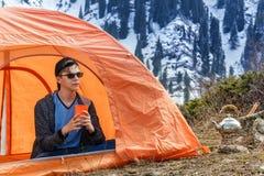 De jonge kerel met een glas thee of koffie zit in een toeristentent bij een halt in de bergen tegen de achtergrond van snow-cover stock foto's