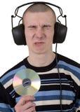 De jonge kerel met oortelefoons en een compact-disc stock foto