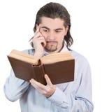 De jonge kerel onderzoekt boek en denkt geïsoleerde Stock Afbeeldingen