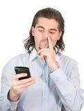 De jonge kerel plukt zijn neus en houdt celtelefoon Stock Afbeelding