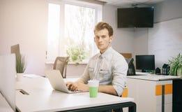De jonge kerel zit bij de computer in het bureau met de vensters achter zijn rug stock afbeeldingen