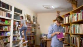 De jonge kerel zoekt een boek op de plank in de bibliotheek stock videobeelden