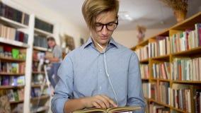 De jonge kerel zoekt een boek op de plank in de bibliotheek stock footage