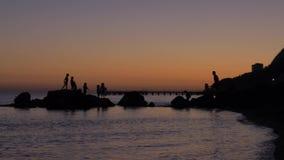 De jonge kinderen spelen op de rotsen op het strand door het overzees bij zonsondergang Silhouetten van kinderen die op de rotsen stock videobeelden