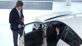 De jonge klant inspecteert een auto in het autohandel drijven stock video