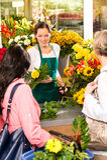 De jonge klanten van de de bloemwinkel van de vrouwenbloemist scherpe Stock Afbeeldingen