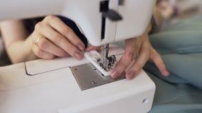 De jonge kledingsontwerper en de naaistersvrouw werken met naaimachineclose-up in kleermakersstudio stock videobeelden