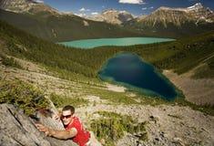 De jonge klimmer bereikt voor houvast in bergen Royalty-vrije Stock Foto's