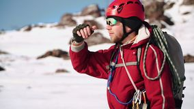 De jonge klimmer van Kaukasische verschijning met een baard die zich op een sneeuwhelling bevindt kijkt rond en stelt zijn ogen v stock video