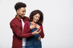 De jonge knappe Afrikaanse Amerikaanse mens vraagt haar meisje om verrassend voorstel royalty-vrije stock foto