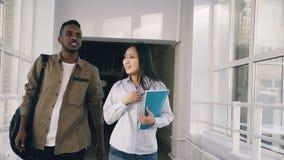 De jonge knappe afro mannelijke student en zijn meisje lopen in universiteitsgang besprekend iets zij komen samen stock video