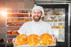 De jonge knappe bakkersholding bakte vers croissants in handen op de achtergrond van de oven stock foto