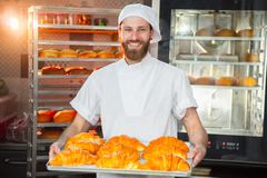 De jonge knappe bakkersholding bakte vers croissants in handen op de achtergrond van de oven royalty-vrije stock afbeeldingen