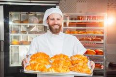 De jonge knappe bakkersholding bakte vers croissants in handen op de achtergrond van de oven stock afbeeldingen