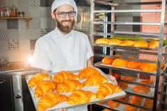 De jonge knappe bakkersholding bakte vers croissants in handen op de achtergrond van de oven royalty-vrije stock foto's