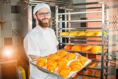 De jonge knappe bakkersholding bakte vers croissants in handen op de achtergrond van de oven stock afbeelding